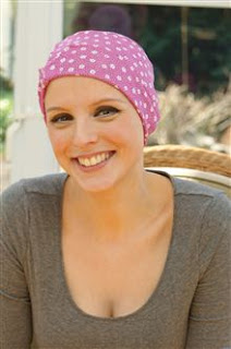 girl smiling wearing pink and white chemo sleep hat