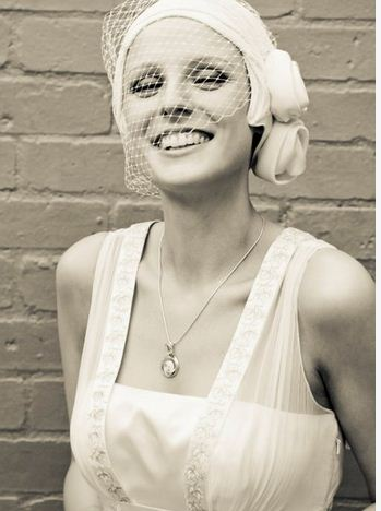 smiling bride wearing cream turban hat with veiling