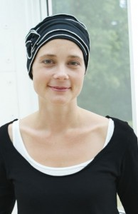 young woman wearing black and white chemo hat
