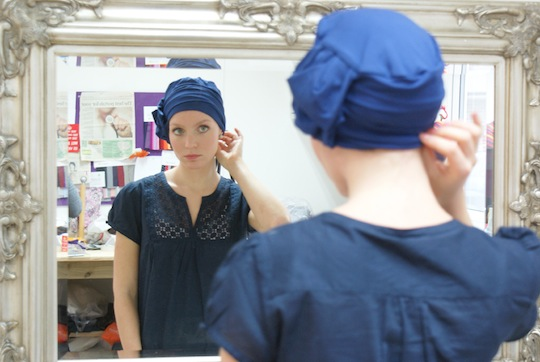 model looking at her reflection in the mirror wearing a blue hat