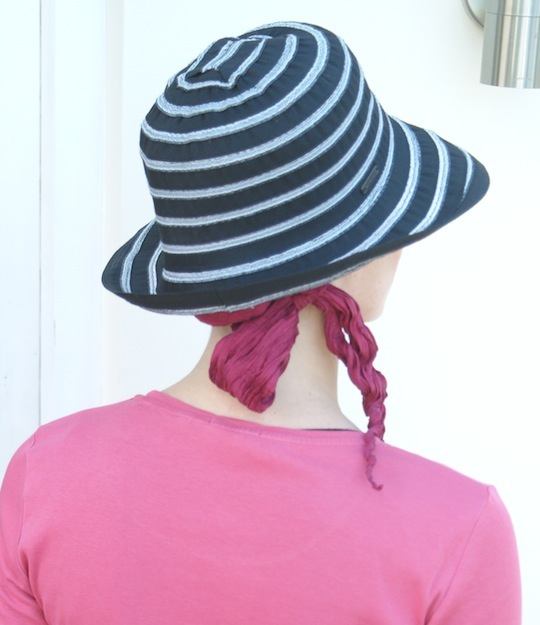 back view of black summer hat worn over pink head scarf