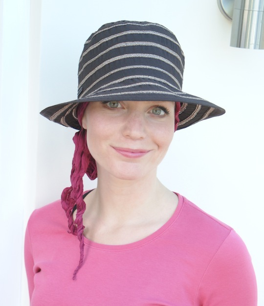 woman wearing brown summer hat over bandana scarf for female hair loss