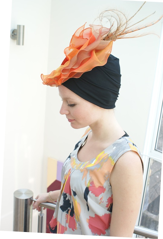woman wearing orange Ascot perch hat over black turban
