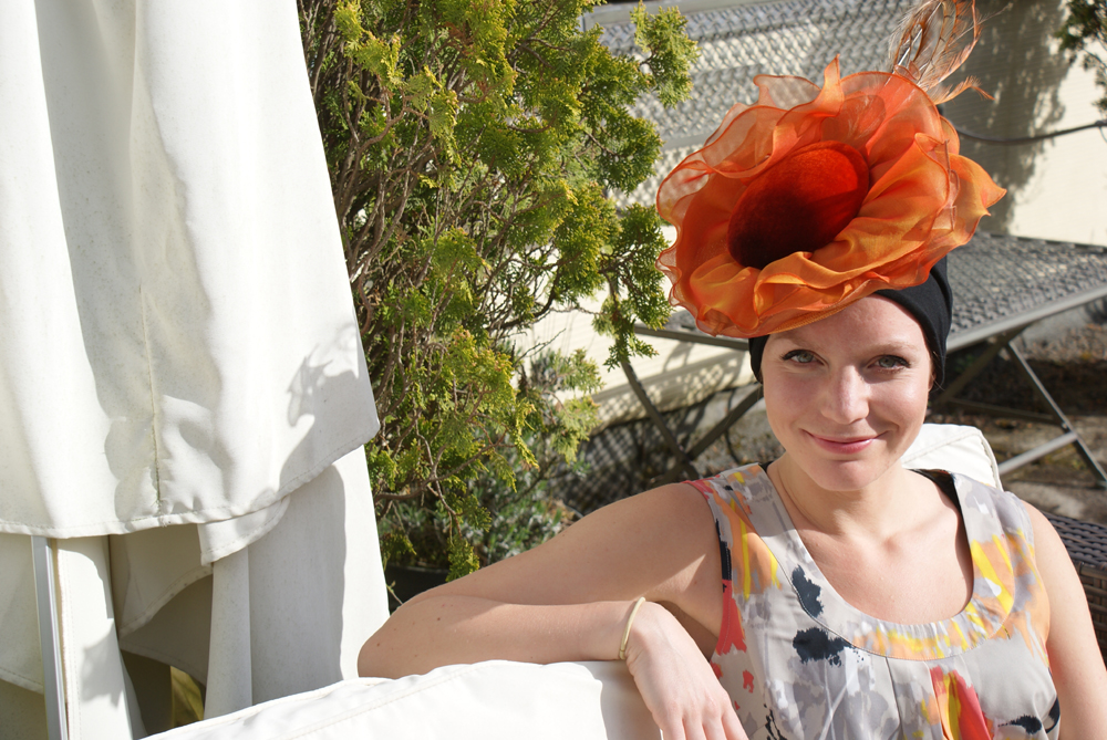 woman sitting in garden wearing orange Ascot hat over turban for hair loss