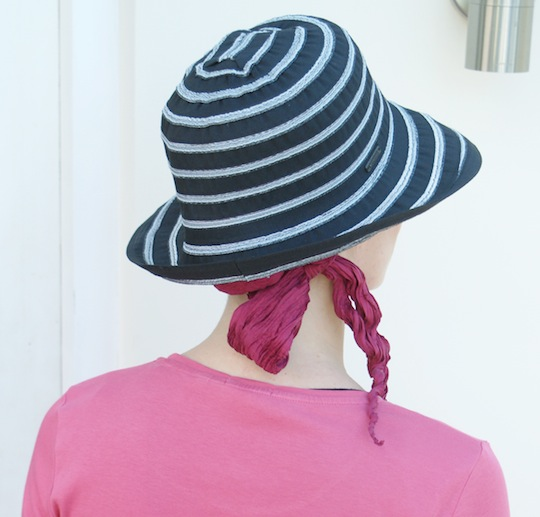 back view of black summer hat with pink scarf worn underneath