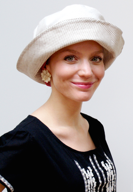 woman smiling wearing cream linen cloche hat with flower earring