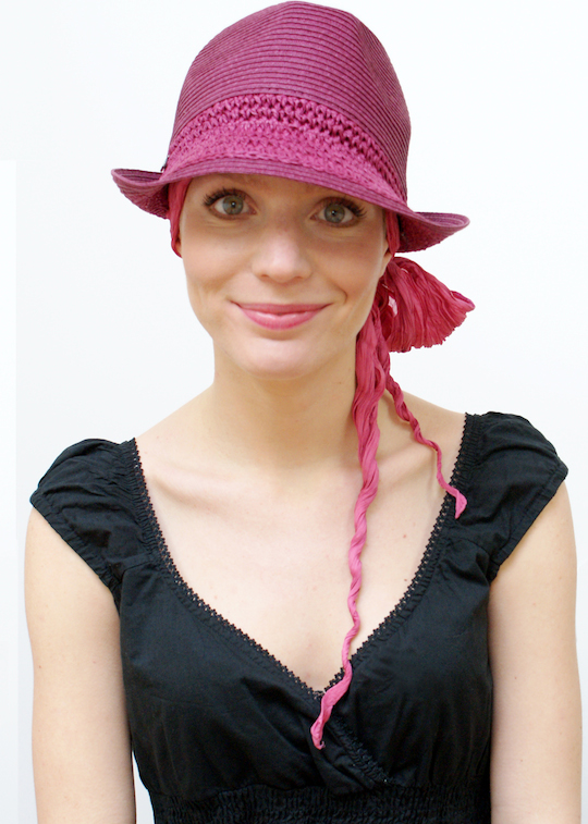 pink trilby summer hat worn over bandana scarf by woman