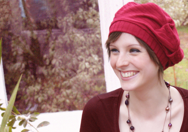 young woman wearing red beret chemo hat smiling