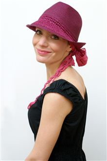 Pink trilby worn by young woman over a headscarf