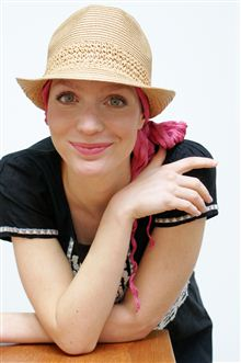 Beige trilby hat worn over pink headscarf on woman smiling