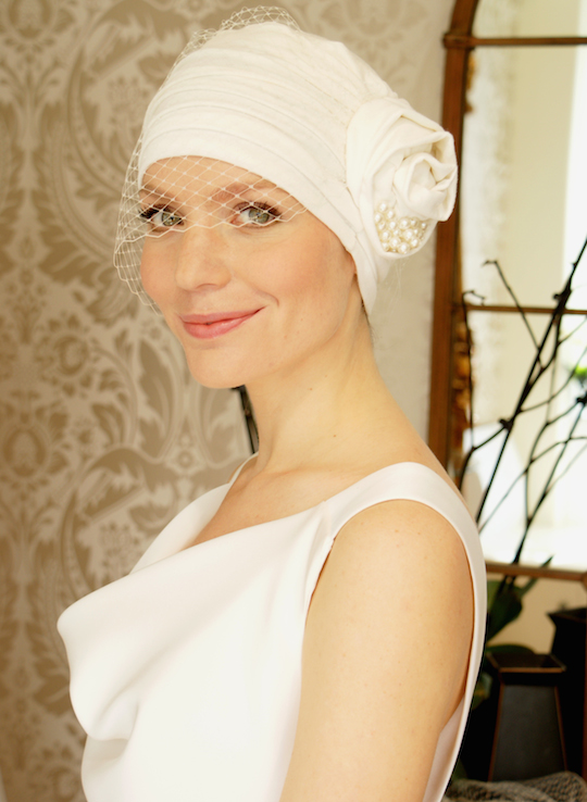 Ivory wedding turban with birdcage veil worn with ivory wedding gown