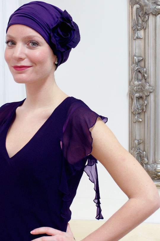 woman wearing purple chemo hat in evening gown