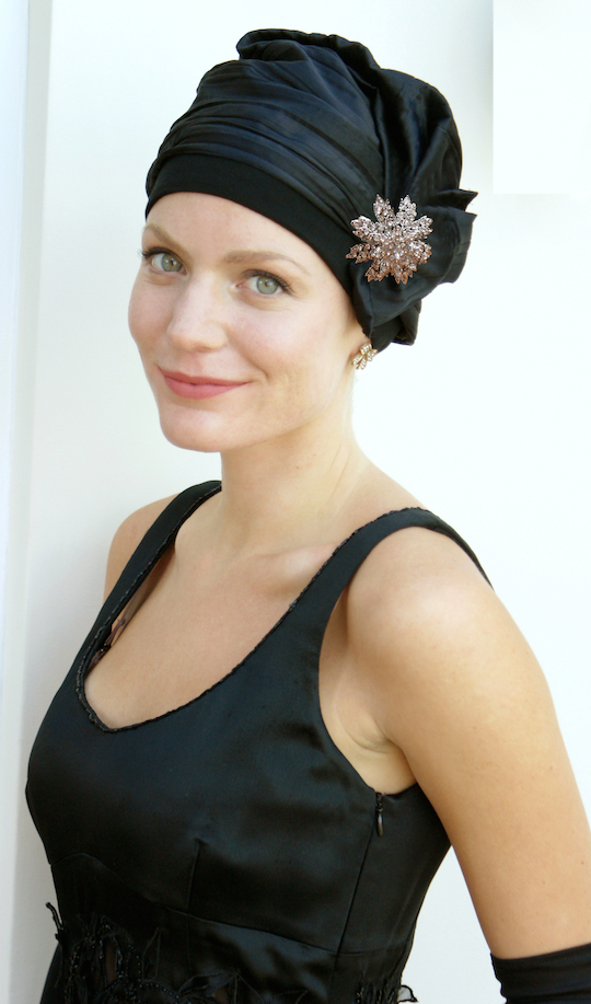 black evening hat with crystal brooch worn by woman in black dress
