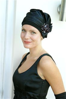 black evening hat with brooch worn by woman in black dress