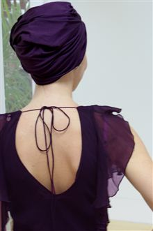 back view of woman wearing a purple hat and dress
