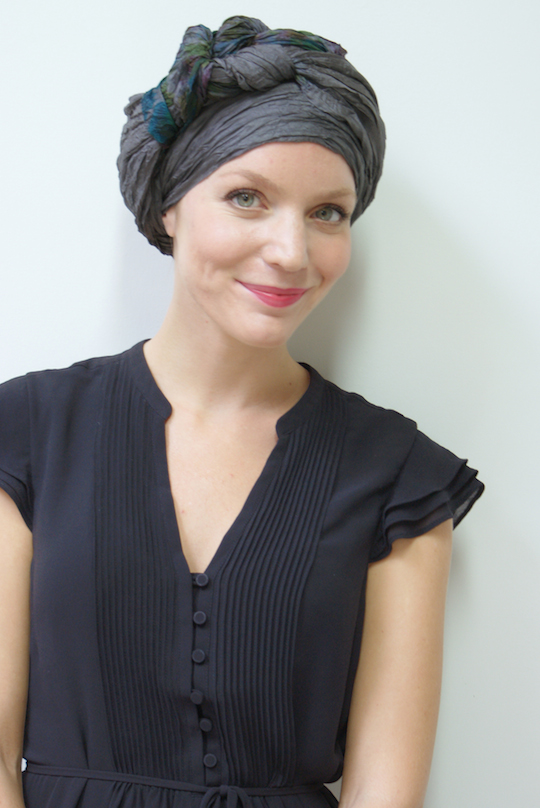 grey silk headscarf worn by woman as a turban on her head