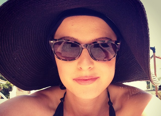 woman wearing large black hat and sunglasses