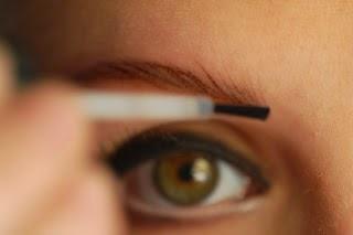 close up of woman's eye applying make-up