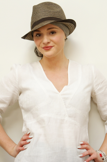 brown trilby hat worn by woman over a grey headscarf standing