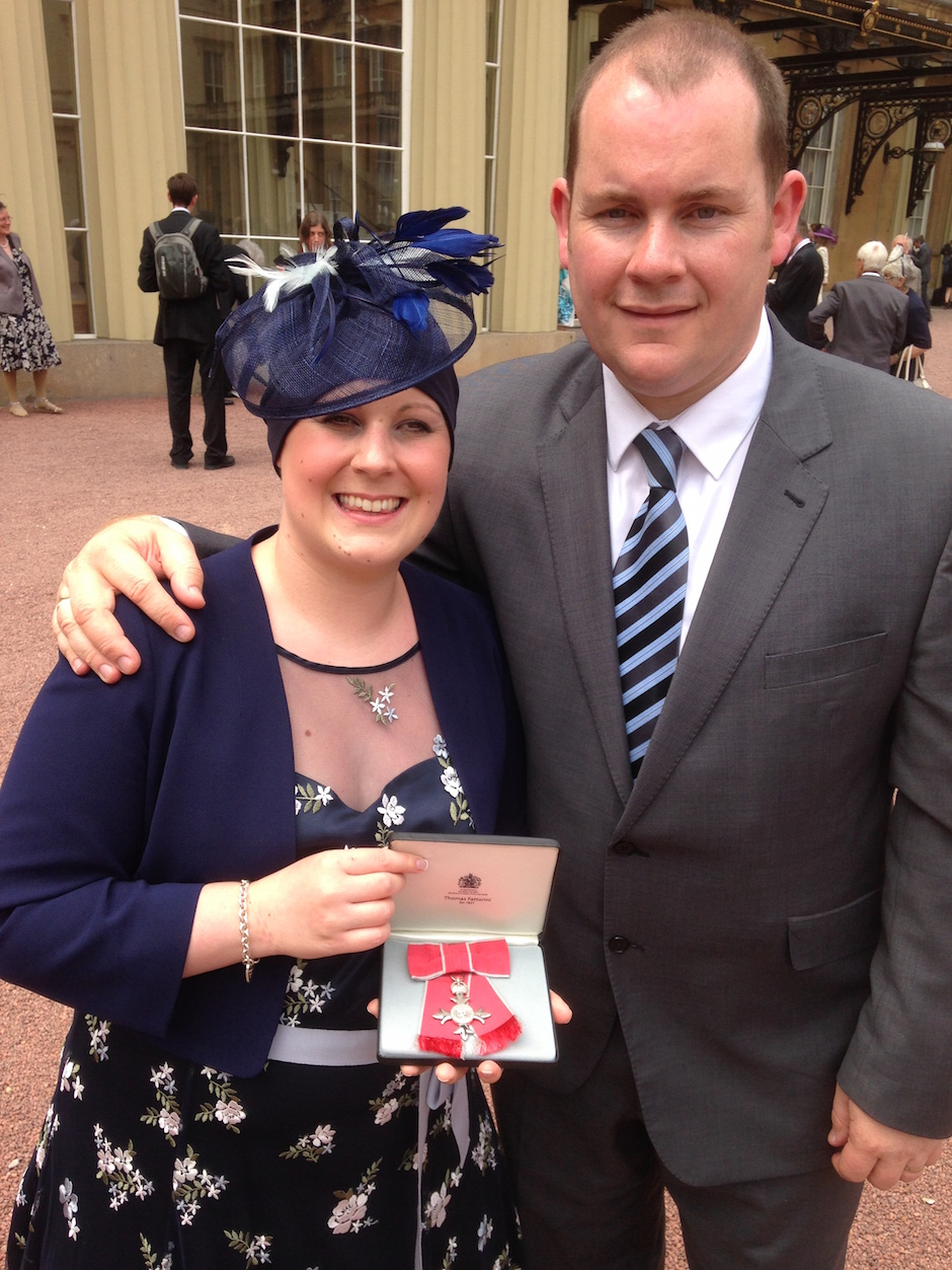 young couple standing in front of Buckingham Palace receiving medal