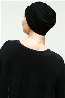 Back view of black turban worn with black evening dress