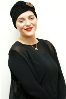 Classic black evening turban worn with gold brooch