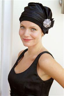 Black satin turban with crystal pin on woman wearing a black evening dress