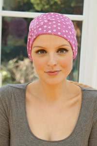 woman seated wearing pink sleep hat with chemo hair loss
